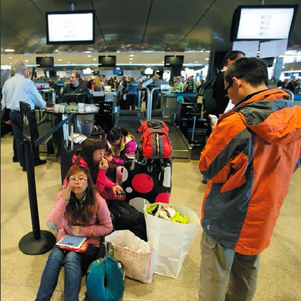 Passengers wait for a delayed flight at an airport. Despite the nation's leading role in the world economy, its transportation system lacks reliability.