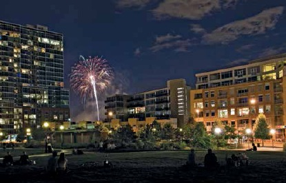 Riverfront Park at night, with Park Place Lofts on the right, the Glass House on the left, and Commons Park in the foreground. The park offers a highly attractive amenity directly adjacent to the project.