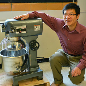 Xianming Shi with the industrial size mixer he uses to concoct green deicers and ice-free pavement. (Photo by Rebecca Phillips, University Communications)